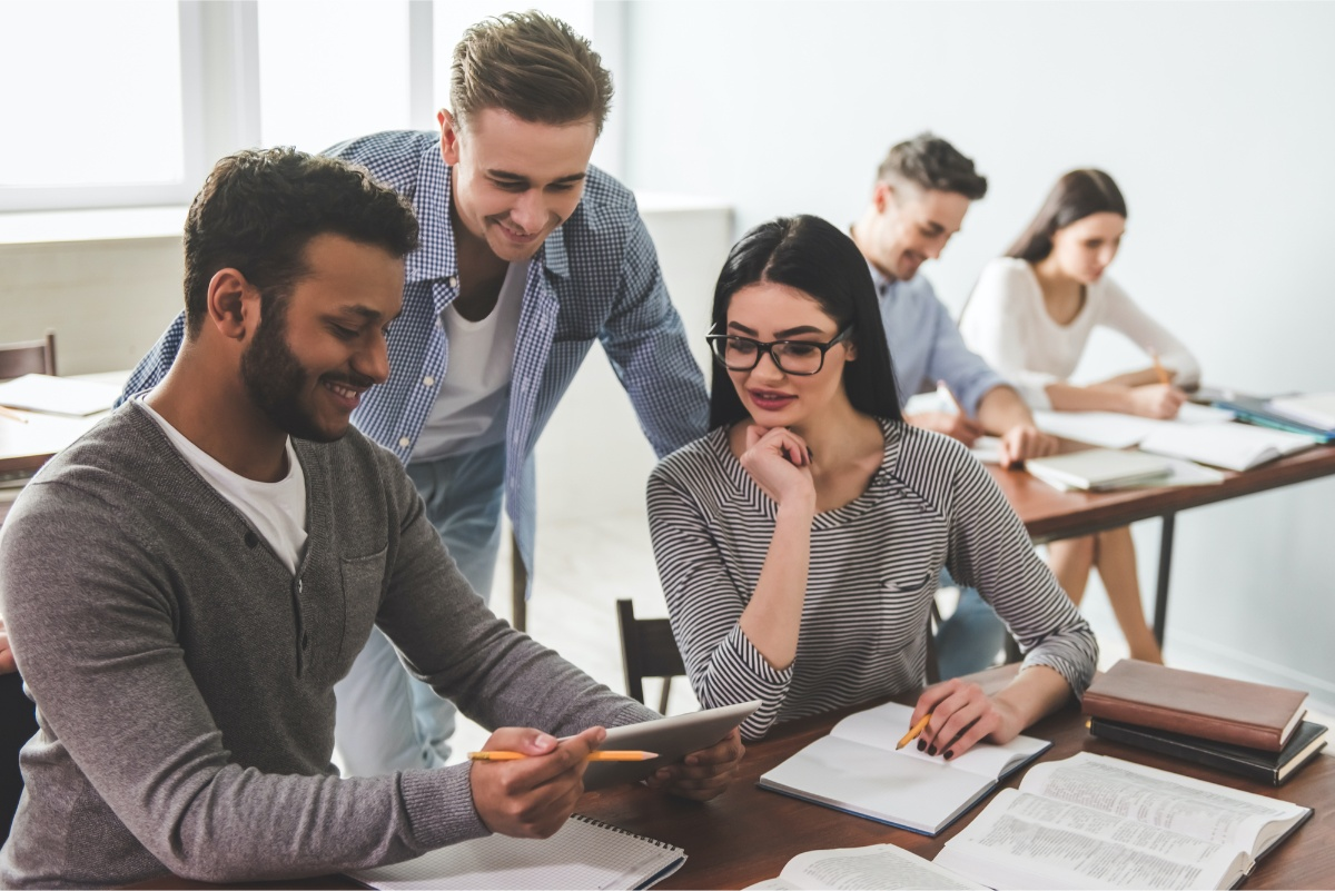employees reviewing ipad together in office