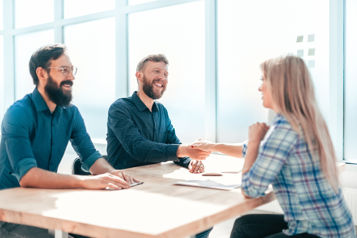 Employees shaking hands at company office business casual