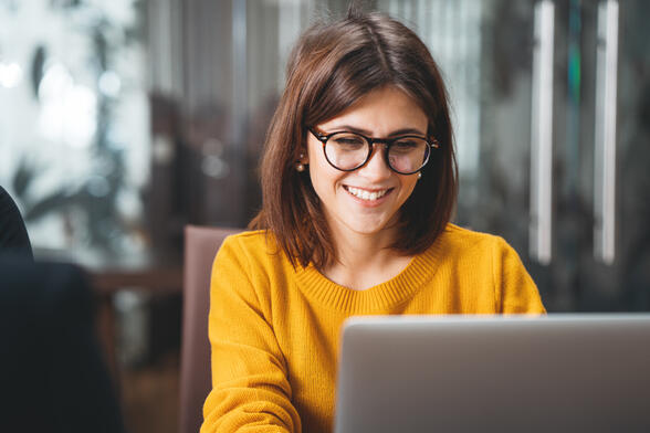 woman in glasses looking at computer