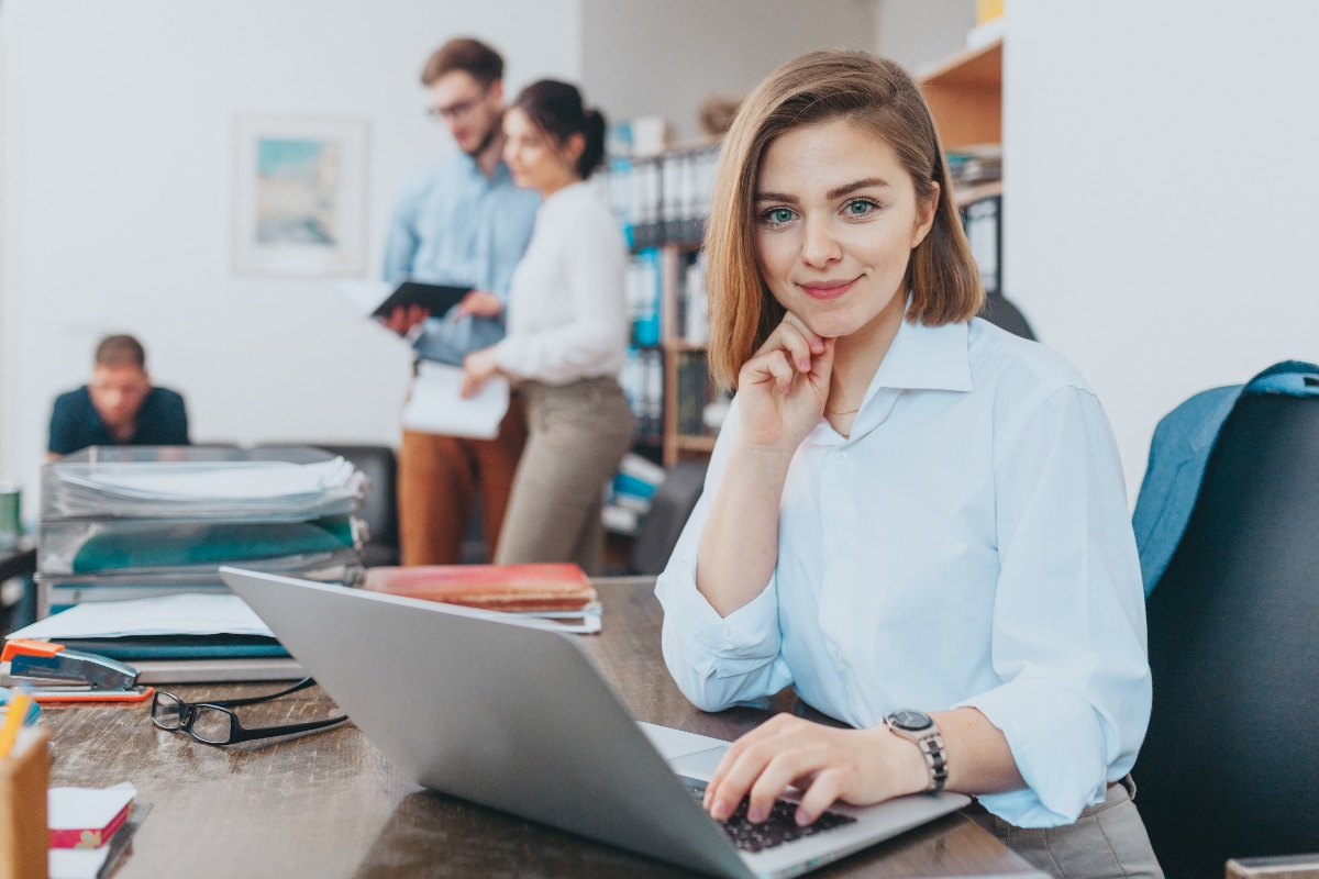 business woman on computer looking at camera in office