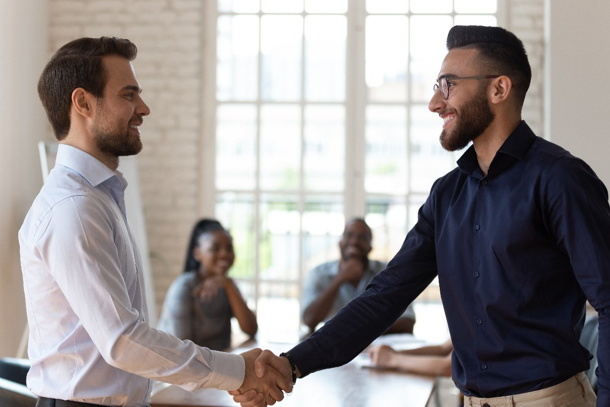 two office men shaking hands greeting each other