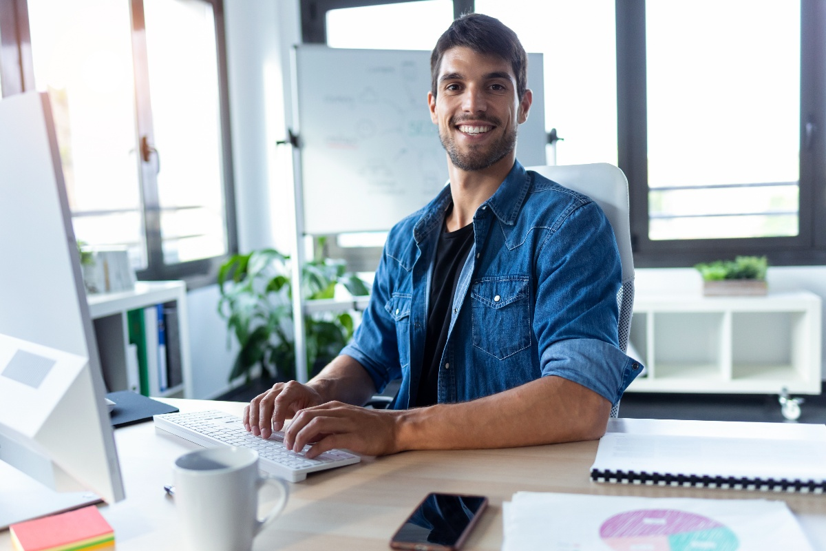 young man on computer in office smiling at camera